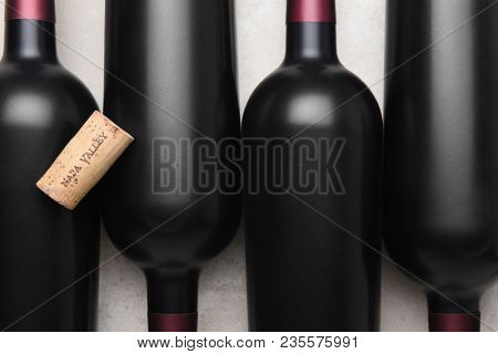 Napa Valley Cork: A wine cork on top of bottles of red wine.