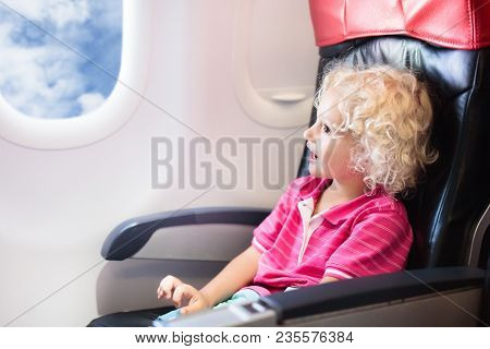 Child In Airplane. Kid In Air Plane Sitting In Window Seat. Flight Entertainment For Kids. Traveling