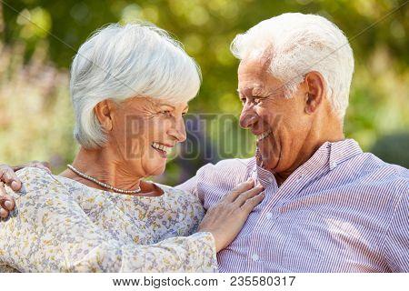 Happy senior couple in garden embracing, head and shoulders