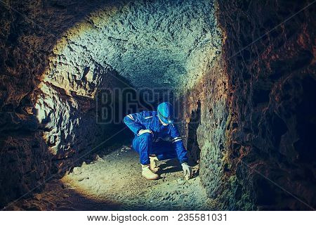 Man Work Underground In Dark Tunnel. Staff  In A Protective Suit Check Sediments In Rocky Wall, Larg