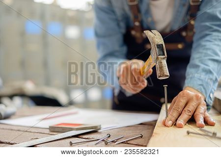 Carpenter Working On Woodworking Machines In Carpentry Shop. A Man Works In A Carpentry Shop.