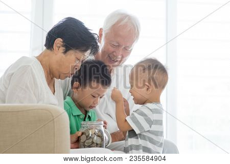 Asian old people and children saving money at home. Family financial planning, investment, insurance, retirement, senior and junior banking concept.