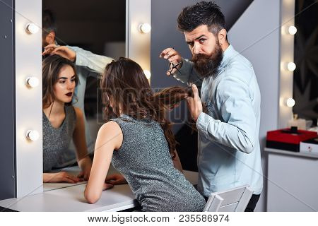 Pretty Girl At Hair Saloon With Male Hairdresser. Brunette Girl With Long And Shiny Wavy Hair. Beaut