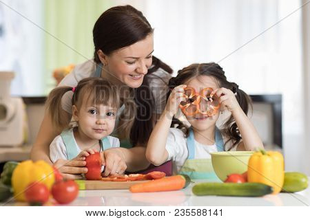 Happy Family Mom And Kids Preparing Vegetables Together At Home In The Kitchen