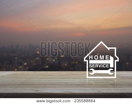 Hammer And Wrench With House Icon On Wooden Table Over Blur Of Cityscape On Warm Light Sundown, Busi