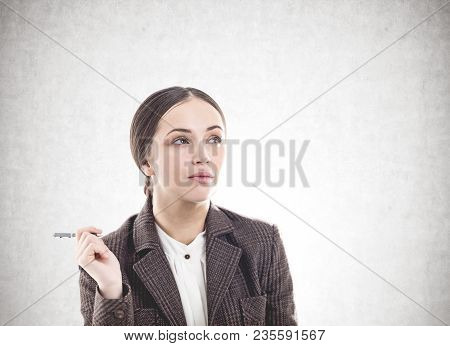 Pensive Young Businesswoman Wearing A Suit Is Holding A Pen And Thinking. Concept Of Business Planni