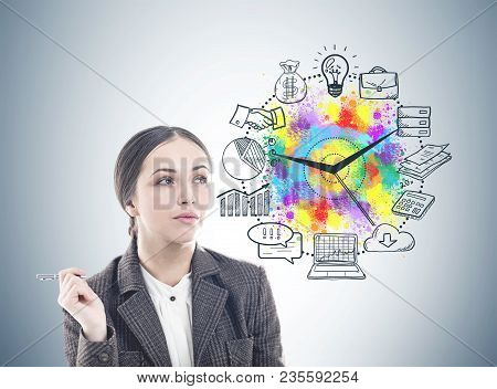 Pensive Young Businesswoman Wearing A Suit Is Holding A Pen And Thinking. A Gray Wall With A Time Ma