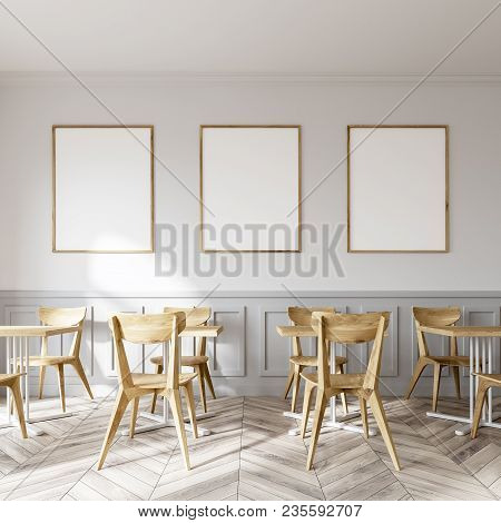 White Restaurant Interior With A Wooden Floor And Square Tables With White Wooden Chairs Near Them.