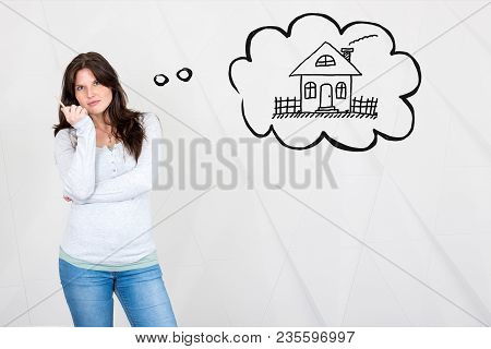 Dreamy Young Woman Thinking Of Owning A House Symbolized By House In Thought Bubble With Pencil In H