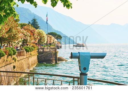 Public Telescope At Observation Point In Beautiful Bellagio Town At Lake Como In Italy With Blooming