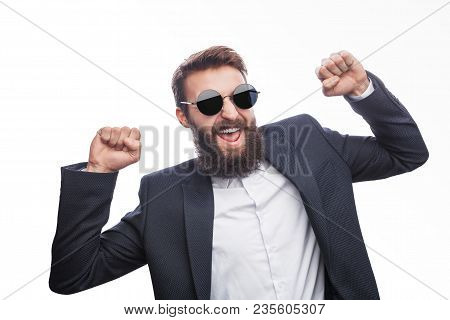 Super Excited Bearded Guy In Suit And Sunglasses Holding Fists Up And Laughing On White Background.