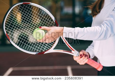 Female Hand Holding Tennis Ball And Tennis Racket, Prepare To Serve. Tennis Player Starting Set