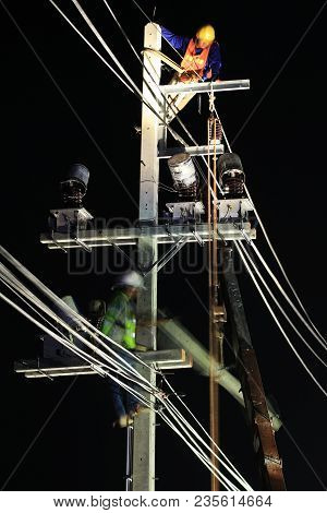 Technicians Working On Electrical Pole At Night