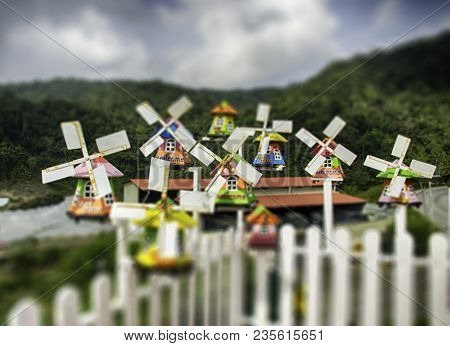 Group Of Miniature Traditional Dutch Old Wooden Windmill With Top Hill View, Cloudy Sky And Hill Bac