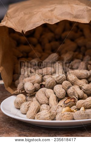 Whole Peanuts Being Spilled Out Of A Brown Paper Bag.