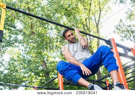 Low-angle view of a powerful young man doing one-arm pull-ups, while hanging on a bar during extreme workout in a modern calisthenics park