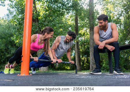 Low-angle view of a young determined couple in love doing push-ups together in a modern calisthenics park next to their friend
