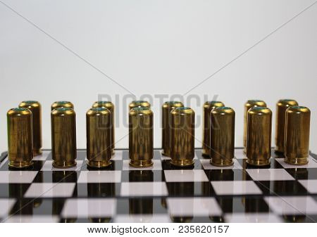 Abstract Photo With Metal Brass Gold Gun Bullets Hubs On Chessboard