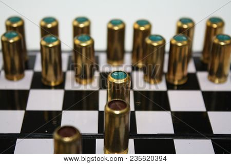 Brass Bullets Gun Munition On Black And White Chessboard Desk