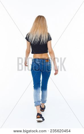 back view of walking woman. beautiful girl in motion. backside view of person.  Rear view people collection. Isolated over white. Blonde in a short T-shirt goes into the distance
