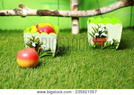 Green Artificial Grass In The Photo Studio. On The Grass In Pots And Artificial Fruits.