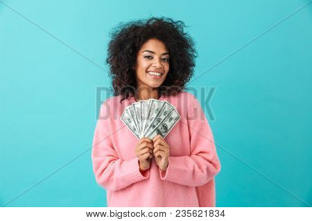 Portrait of rich curly woman 20s with afro hairstyle holding lots of money dollar currency isolated over blue background