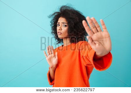 Colorful image closeup of determined woman expressing perplexity and confusion with showing stop gestures and saying no isolated over blue background