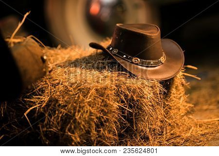 Leather Cowboy Hat On The Small Pile Of Hay In The Old Barn. Western Wear And Wild West Concept.