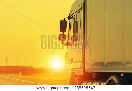 Road Shipping By Semi Truck. Heavy Load Long Haul Euro Transportation Theme. Sunset On The Highway.