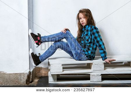 Female Teenager Sits On Pallets Near White Concrete Wall. Girl Hipster Child In Bright Blue Shirt In