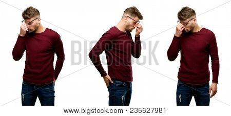 Handsome blond man with sleepy expression, being overworked and tired, rubbes nose because of weariness isolated over white background