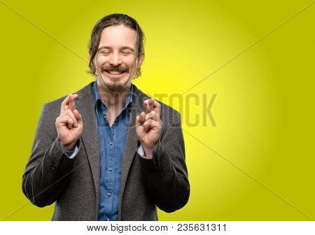 Handsome young man with crossed fingers asking for good luck