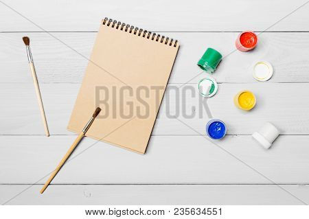Gouache Watercolor Paint. Drawing Paintbrush On Paper Notebook. White Wooden Background