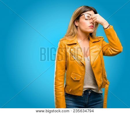 Beautiful young woman with sleepy expression, being overworked and tired, rubbes nose because of weariness, blue background