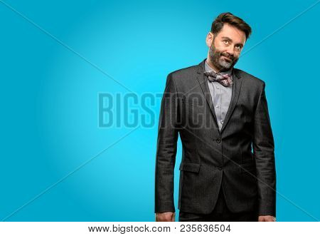 Middle age man, with beard and bow tie with sleepy expression, being overworked and tired