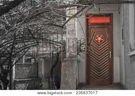 Wooden Entry Door On A House With Reversed Pentagram