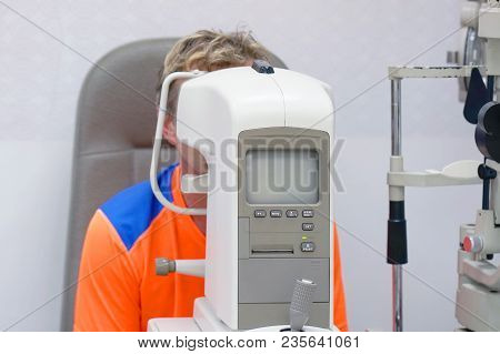 Health Care, Medicine, People, Eyesight And Technology Concept - Man Checks His Vision On The Machin