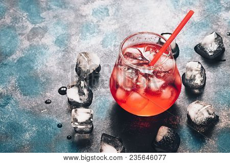 Red Cocktail With Ice On A Black Blue Surface. Bright, Red Drink In Backlight. Copy Space