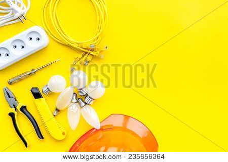 Electrician Work Concept. Hard Hat, Tools, Cabel, Bulb, Socket Outlet On Yellow Background Top View.