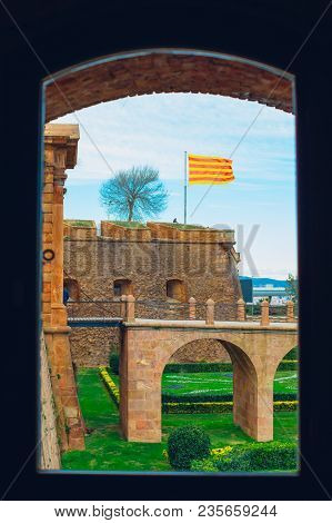 View From The Window Of The Montjuic Fortress On The Flag Of Catalonia Waving At The Fortress