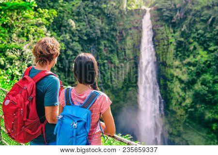 Hawaii travel tourists at nature waterfall landscape. Travelers couple looking at Akaka Falls in Big Island, Hawaiian famous attraction, USA.