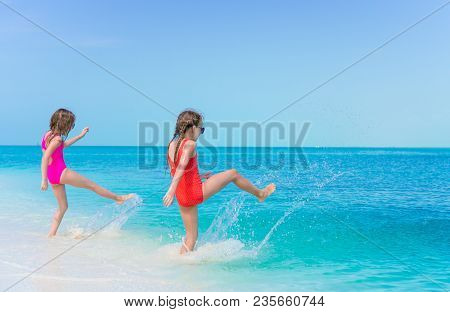 Little Girls Having Fun At Tropical Beach Playing Together At Shallow Water. Adorable Little Sisters