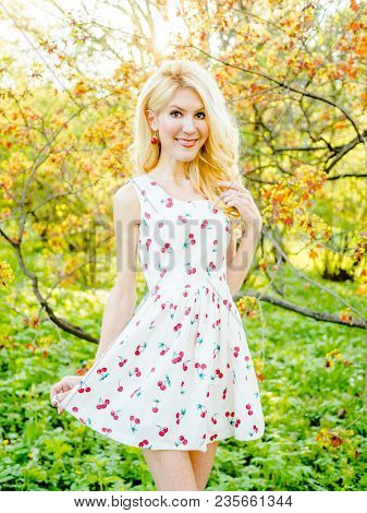 Blonde In A White Summer Dress On A Background Of Flowering Garden