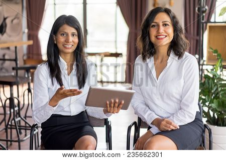 Portrait Of Cheerful Multiethnic Female Colleagues Meeting In Lounge Room. Young Caucasian And Latin