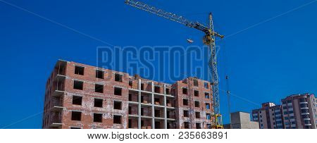 Construction Site Of A New Apartment High Building With Tower Cranes Against Blue Sky. Residential A