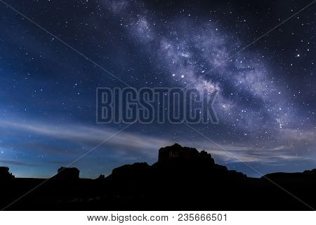 With The Coming Glow Of Sunrise Silhouetting Rock Formations On The Horizon, The Milky Way Decorates
