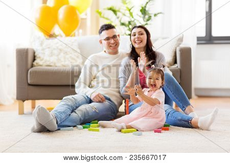 family, holidays and people concept - happy mother, father and little daughter clapping hands at home