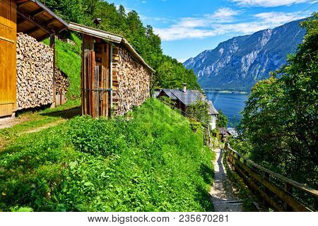Hallstatt, Austria. Wood stacks with stacked firewood stock for winter heating. Walking path to Hallstattersee lake.