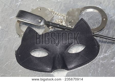 Mysterious Erotic Pleasure Things Concept. Cat Eye Mask, Whip And Hand Cuffs. Fetish Role Playing.