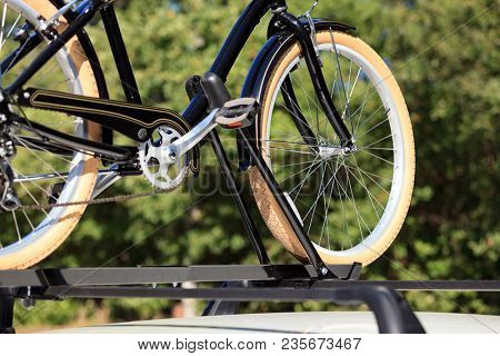 Bicycle on the roof of white car